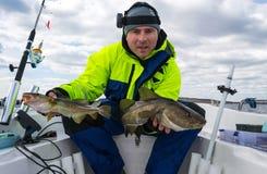 Lycklig sportfiskare med två baltiska torskar Arkivbilder