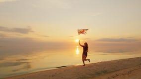 Lycklig spring för ung kvinna med en drake ural town för bergsimsolnedgång arkivfilmer
