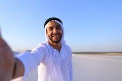 Lycklig stående av den manliga araben, som ler och jublar liv, standi Royaltyfri Fotografi