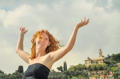 Lycklig lycklig stående av en ung elegant rödhårig lockig kvinna med armar som lyfts på sjösidan på stranden i Italien med kopian arkivfoto