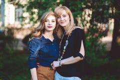 lycklig stående för familj dotter som kramar modern Arkivbilder