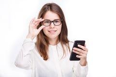 Lycklig stående och att le kvinnan som smsar på hennes smarta telefon, isolerad vit bakgrund svart telefon för kommunikationsbegr Arkivfoto