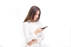 Lycklig stående och att le kvinnan som smsar på hennes smarta telefon, isolerad vit bakgrund svart telefon för kommunikationsbegr Royaltyfria Bilder