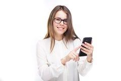 Lycklig stående och att le kvinnan som smsar på hennes smarta telefon, isolerad vit bakgrund svart telefon för kommunikationsbegr Arkivbilder