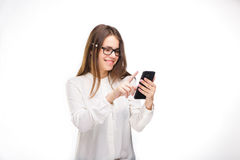 Lycklig stående och att le kvinnan som smsar på hennes smarta telefon, isolerad vit bakgrund svart telefon för kommunikationsbegr Royaltyfri Bild