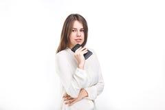 Lycklig stående och att le kvinnan som smsar på hennes smarta telefon, isolerad vit bakgrund svart telefon för kommunikationsbegr Arkivfoton