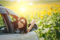 Lycklig stående och att le kvinnasammanträde i bilen som ut ser fönster som är klara för semestertur Arkivfoto