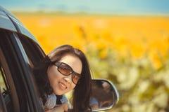 Lycklig stående och att le kvinnasammanträde i bilen som ut ser fönster som är klara för semestertur Arkivbild