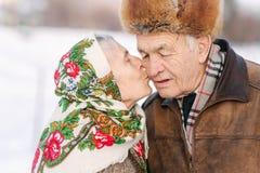 lycklig ståendepensionär för par Äldre kvinnakyss hennes make i weighty gammal parwalkink i parkerar i vinter fotografering för bildbyråer