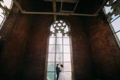 Lycklig stilfull brud och brudgum som rymmer sig i belltoweren av den gamla gotiska domkyrkan Arkivfoton