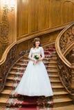 Lycklig stilfull brud som poserar med buketten för vita rosor på bakgrunden av gammal trätrappa Fotografering för Bildbyråer