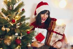 Lycklig stilfull kvinna i den santa hatten som rymmer många gåvaaskar med bo royaltyfria foton