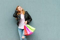 Lycklig stilfull kvinna med shoppingpåsar över grå bakgrund Nätt ung kvinna som tycker om i shopping Consumerism shopping, försäl arkivfoto