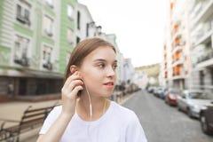 Lycklig stilfull kvinna som går runt om staden och lyssnar till musik i hörlurar arkivbild