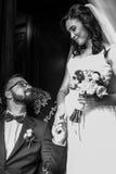Lycklig stilig brudgum på läderstol som rymmer handen av en friare fotografering för bildbyråer