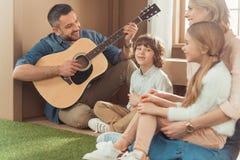 lycklig stilig fader som spelar gitarren för ungar och fru på nytt arkivbilder