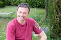 Lycklig stilig man som är utomhus- i hemträdgård arkivfoto