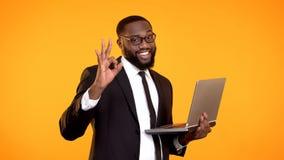 Lycklig stilig svart man i dr?kten som rymmer b?rbara datorn och visar den ok gesten, framg?ng royaltyfria bilder
