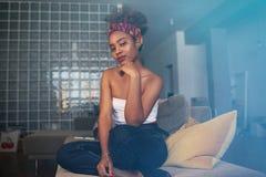 Lycklig stilig ung svart amerikansk afrikan som ?r kvinnlig med den afro- frisyren som hemma kopplar av p? soffan Annonsering och royaltyfri fotografi