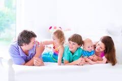 Lycklig stor familj i en säng Arkivbild