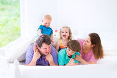 Lycklig stor familj i en säng Royaltyfri Bild