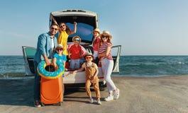 Lycklig stor familj i lopp f?r sommarautomatiskresa med bilen p? stranden arkivbild