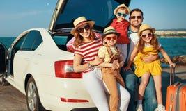 Lycklig stor familj i lopp f?r sommarautomatiskresa med bilen p? stranden royaltyfria bilder