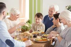 Lycklig stor familj som äter matställen arkivbilder
