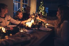 Lycklig storfamilj som har julmatställen hemma arkivbild
