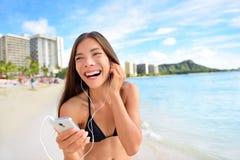 Lycklig strandkvinna som lyssnar till musik på smartphonen Royaltyfria Bilder