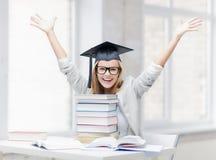 Lycklig student i avläggande av examenlock Arkivbild
