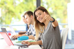 Lycklig student med tummar upp i ett klassrum royaltyfria bilder
