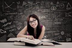 Lycklig student och skriftlig svart tavla arkivbilder