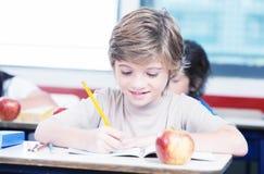 Lycklig student på grundskolahandstil på hans skrivbok arkivfoton