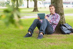 Lycklig student som använder hans minnestavlaPC utanför benägenhet på träd fotografering för bildbyråer