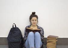 Lycklig student som läser en bok royaltyfri fotografi