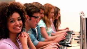 Lycklig student som ler på kameran i datorgrupp stock video
