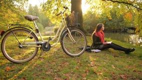 Lycklig studentflicka som kopplar av på gräshandstil i en anteckningsbok Cykeln och härligt offentligt parkerar i bakgrunden stock video