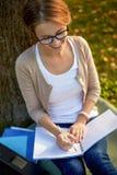 Lycklig studentflicka som skriver till anteckningsboken på universitetsområdet Royaltyfria Bilder