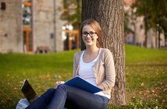 Lycklig studentflicka som skriver till anteckningsboken på universitetsområdet Royaltyfri Foto