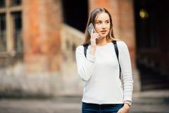 Lycklig studentflicka som utomhus går och kallar på mobiltelefonen med Uni en bakgrund Royaltyfri Fotografi