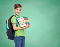 Lycklig studentpojke med skolapåsen och böcker Fotografering för Bildbyråer
