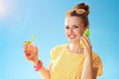 Lycklig sund kvinna med den uppfriskande coctailen genom att använda mobiltelefonen Royaltyfri Foto
