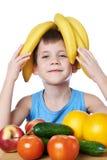 Lycklig sund pojke med isolerade bananer och frukter Royaltyfria Bilder
