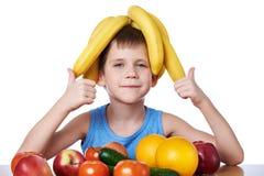 Lycklig sund pojke med isolerade bananer och frukter Arkivbild