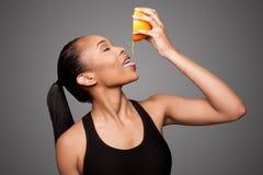 Lycklig sund svart asiatisk kvinna som pressar frukt för orange fruktsaft Fotografering för Bildbyråer