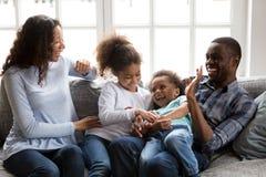 Lycklig svart familj som skrattar att spela killa barn hemma arkivfoton