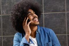 Lycklig svart grabb som talar på mobiltelefonen Fotografering för Bildbyråer