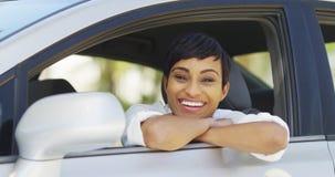 Lycklig svart kvinna som ler och ser ut ur bilfönster Arkivfoton