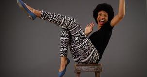 Lycklig svart kvinnadans på stol royaltyfri bild